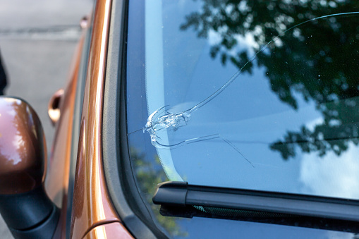 Broken car windshield glass from stone. Damaged windscreen on vehicle, close up