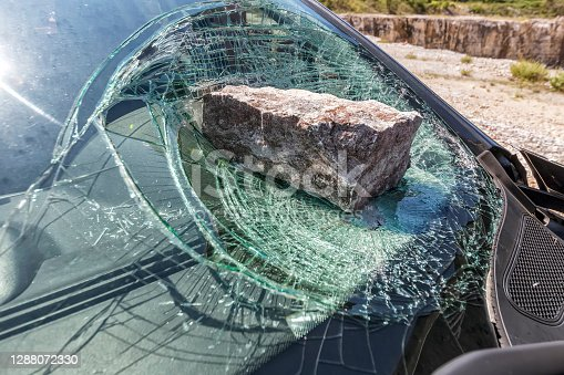 broken car windshield with a huge stone