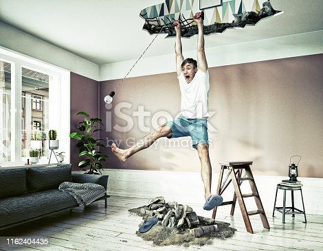 istock broken ceiling and a man hanging in the hole. 1162404435