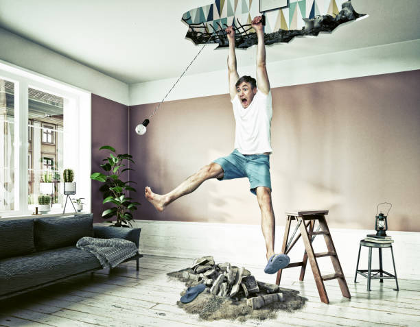 broken ceiling and a man hanging in the hole. stock photo