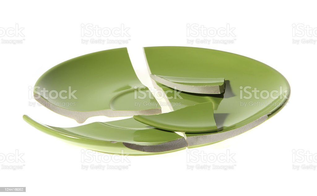 A broken ceramic green plate on a white background stock photo