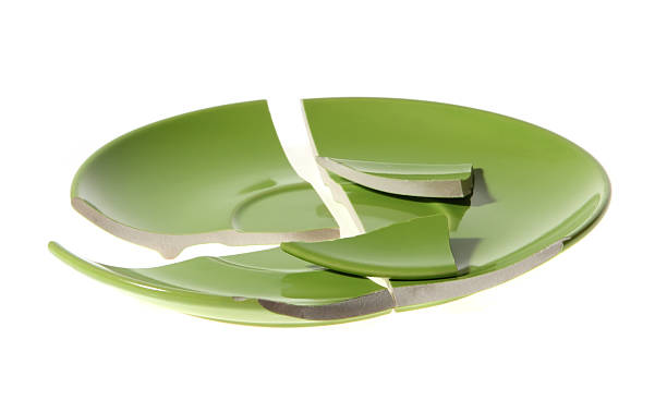 a broken ceramic green plate on a white background - gebroken bord stockfoto's en -beelden