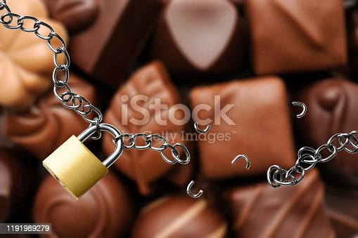 High angle view of broken chain with padlock in front of luxury chocolates. Diet concept.