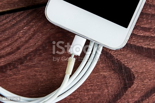 istock Broken Charging Cable With Phone  On A Wooden Background 683911476