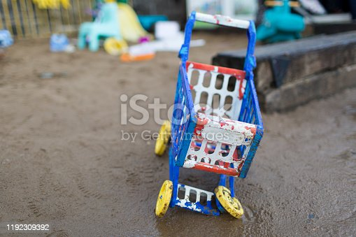 Foreground focus on colourful plastic child's shopping trolley in wet sand.
