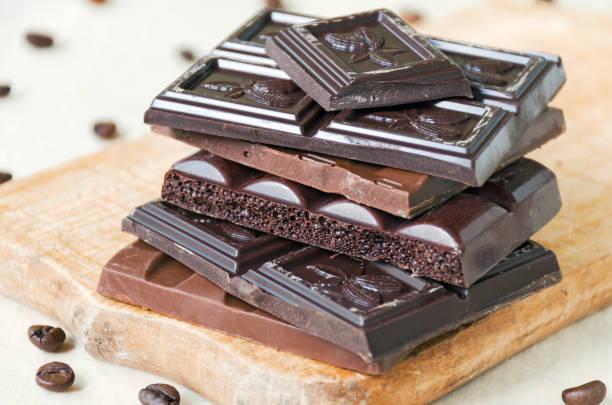 gebroken chocoladerepen van verschillende soorten chocolade zijn gestapeld op een houten plank, een beetje van koffiebonen rond - pure chocola stockfoto's en -beelden