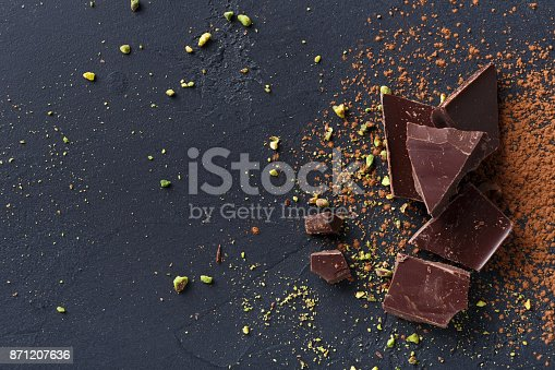 istock Broken chocolate pieces and cocoa powder on black background 871207636