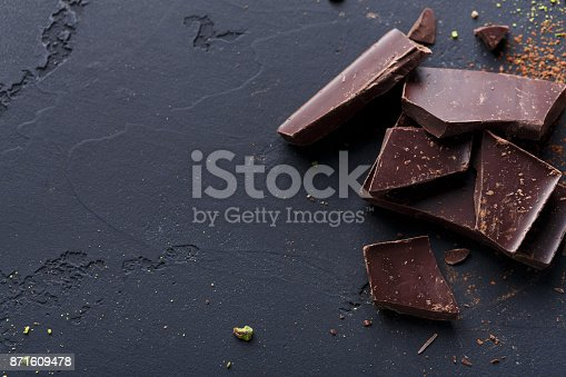 istock Broken chocolate pieces and cocoa powder on black background 871609478