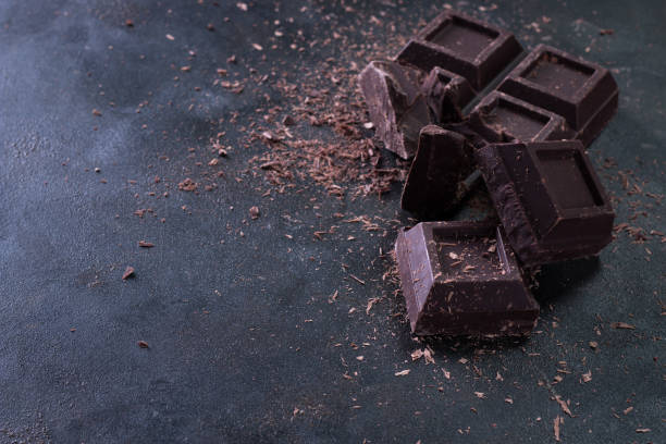 Broken chocolate pieces and cocoa powder on dark background stock photo