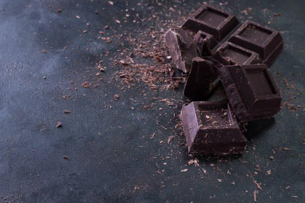 gebroken chocoladestukjes en donkere achtergrond cacao poeder - pure chocola stockfoto's en -beelden