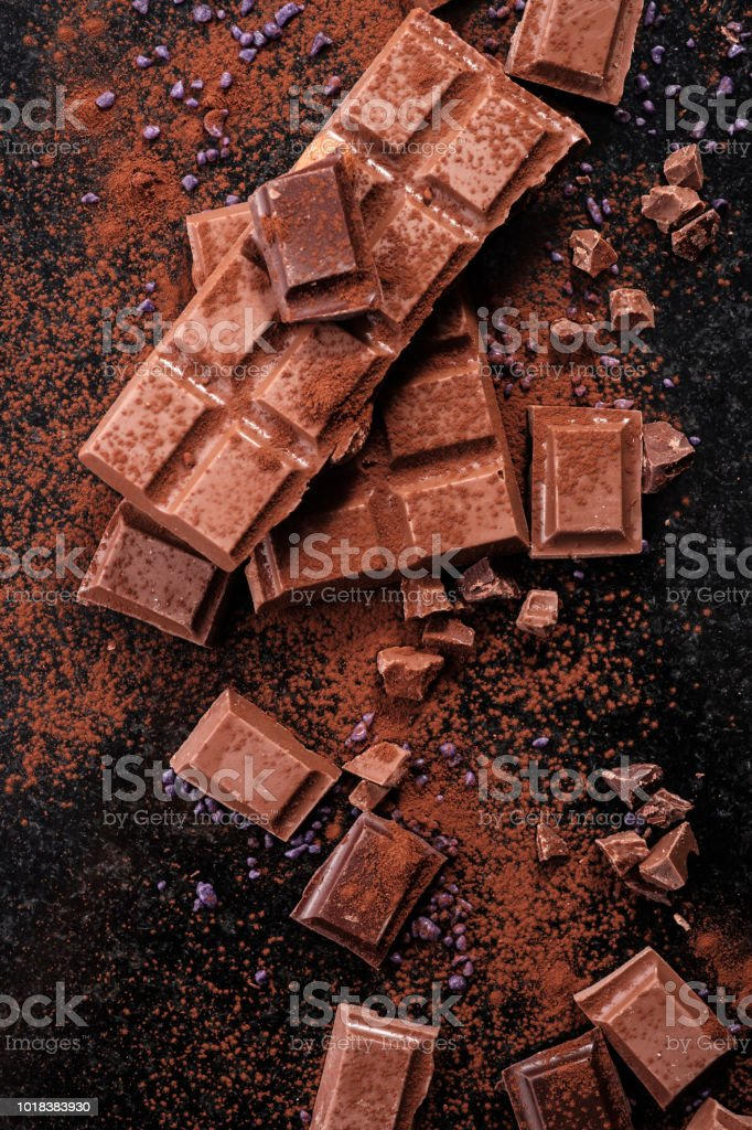 Broken chocolate pieces and cocoa powder on marble. стоковое фото