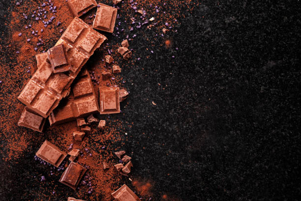Cтоковое фото Broken chocolate pieces and cocoa powder on marble.