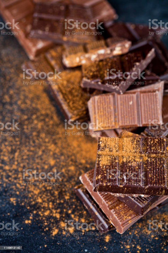Broken chocolate stacked on black background. Chocolate bar pieces...