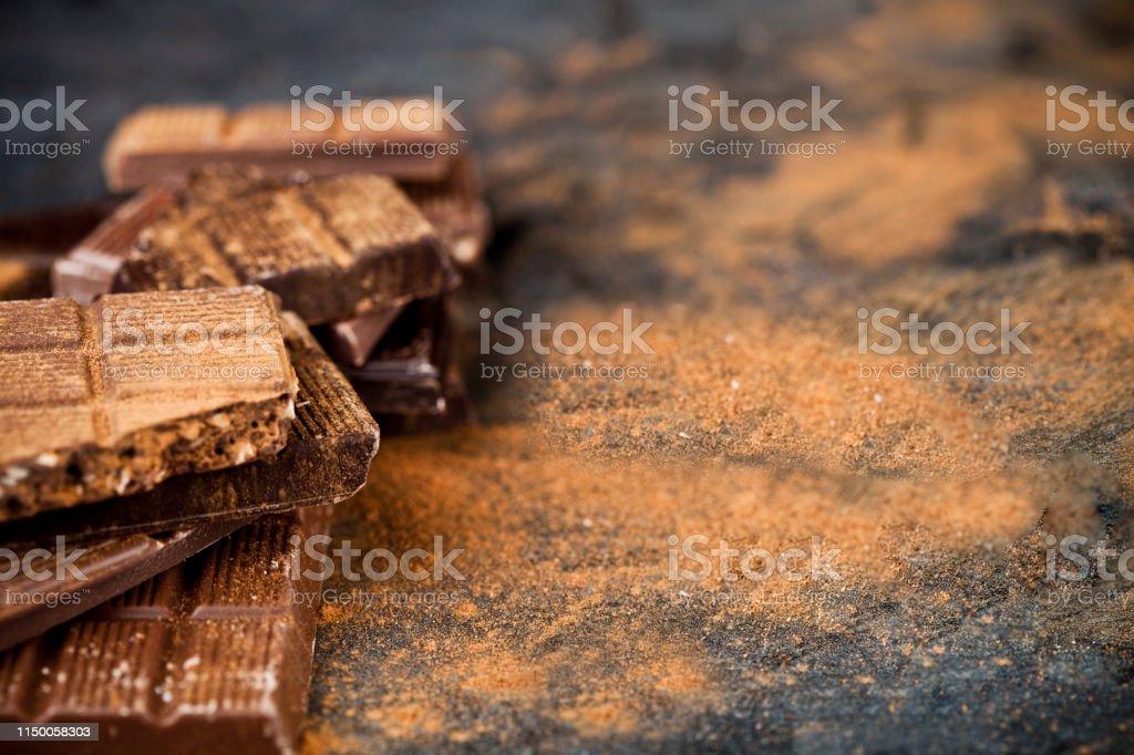 Broken chocolate witn cinnamon powder stacked on black background....
