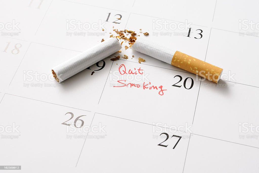 Broken cigarette on a day on calendar, for quit smoking royalty-free stock photo