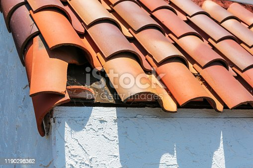 Broken clay roof tile. Exposed under roof tile membrane. Roof inspection, repair and replacement project in progress.