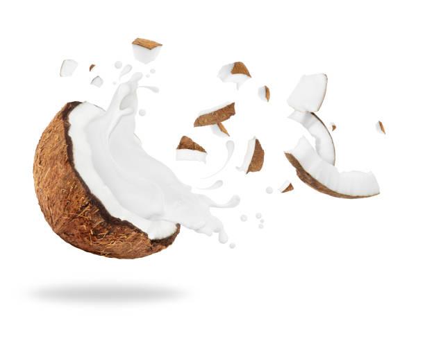 Broken coconut with milk splash, isolated on white background stock photo