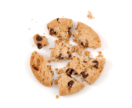 Cookie broken in pieces with crumbs on isolated background.