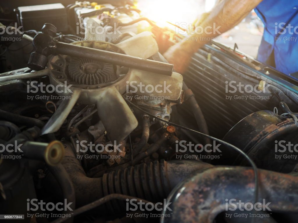 Broken cooling fan motor of car is being removed in garage. Auto repair service. stock photo