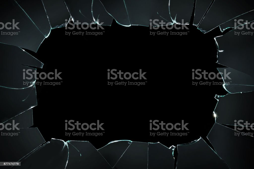 broken cracked glass with big hole over black background stock photo