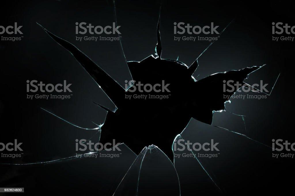 resquebrajados de cristal roto con agujero en el fondo negro - foto de stock