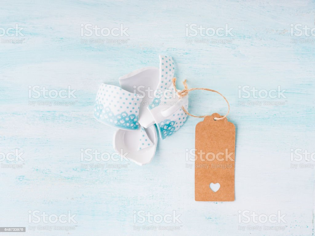 Broken cup relationship concept top view pastel background stock photo
