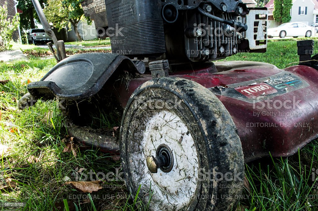 Broken dirty old lawn mower sitting in the yard stock photo