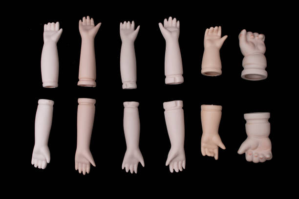 Broken Doll Body Parts Hands and Arms on Black Background stock photo