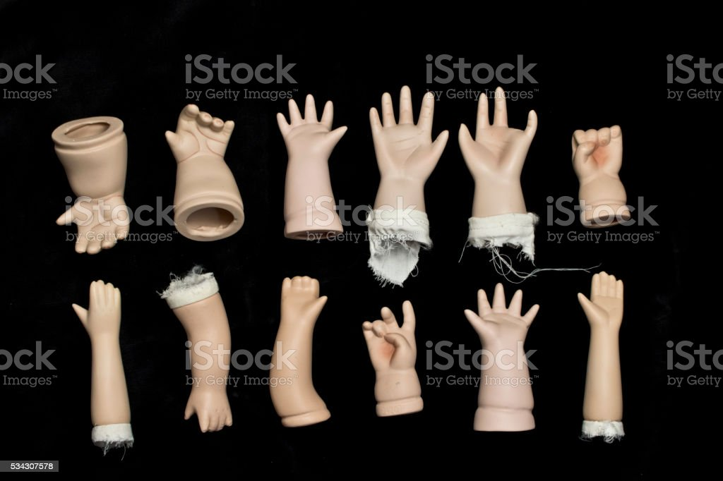 Broken Doll Body Parts on Black Background stock photo