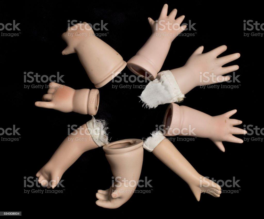 Broken Doll Body Parts on Black Background stock photo