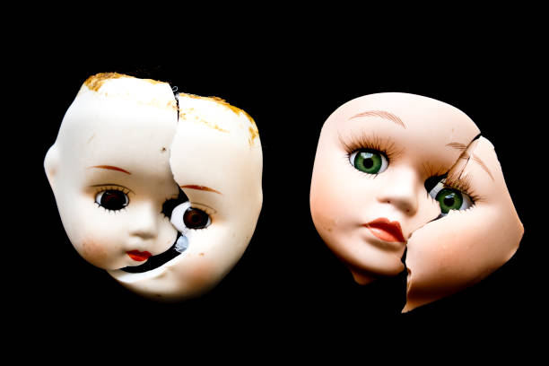 Broken Doll Face and Head on Black Background stock photo