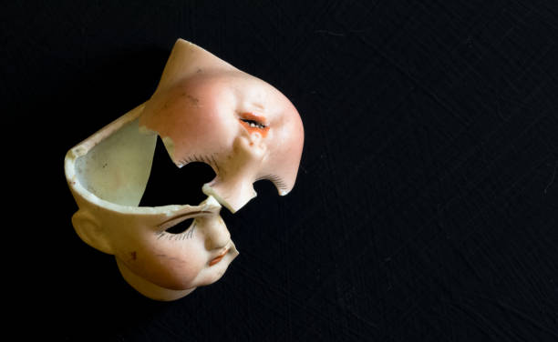 Broken doll face on black background. Conceptual image with two broken ceramic doll faces. stock photo