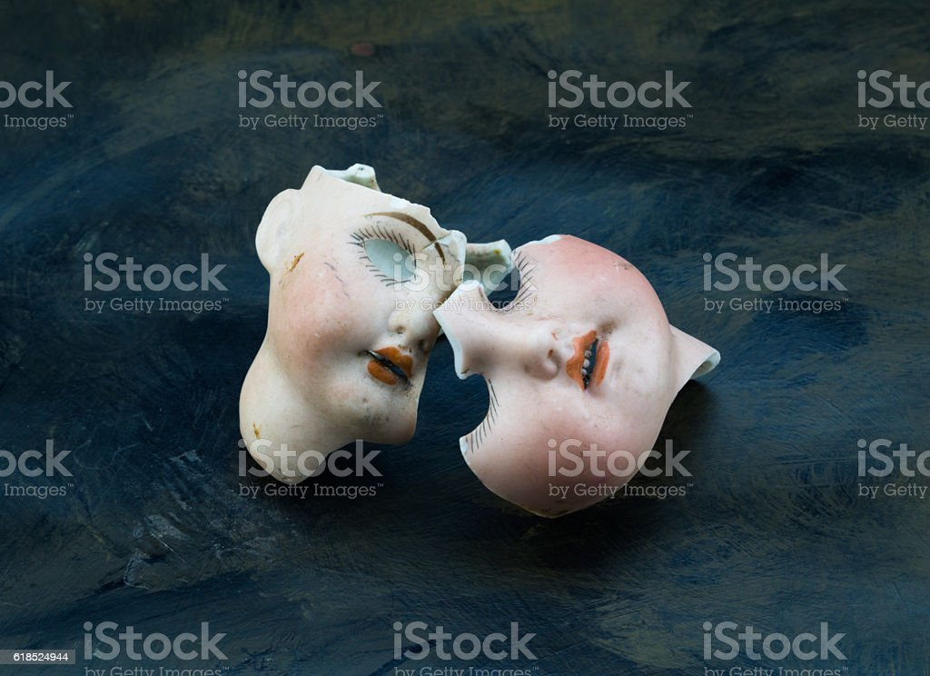 Broken doll faces on grunge background stock photo