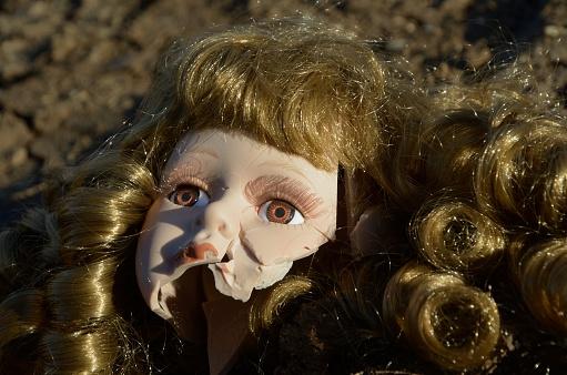 Broken doll head on the ground