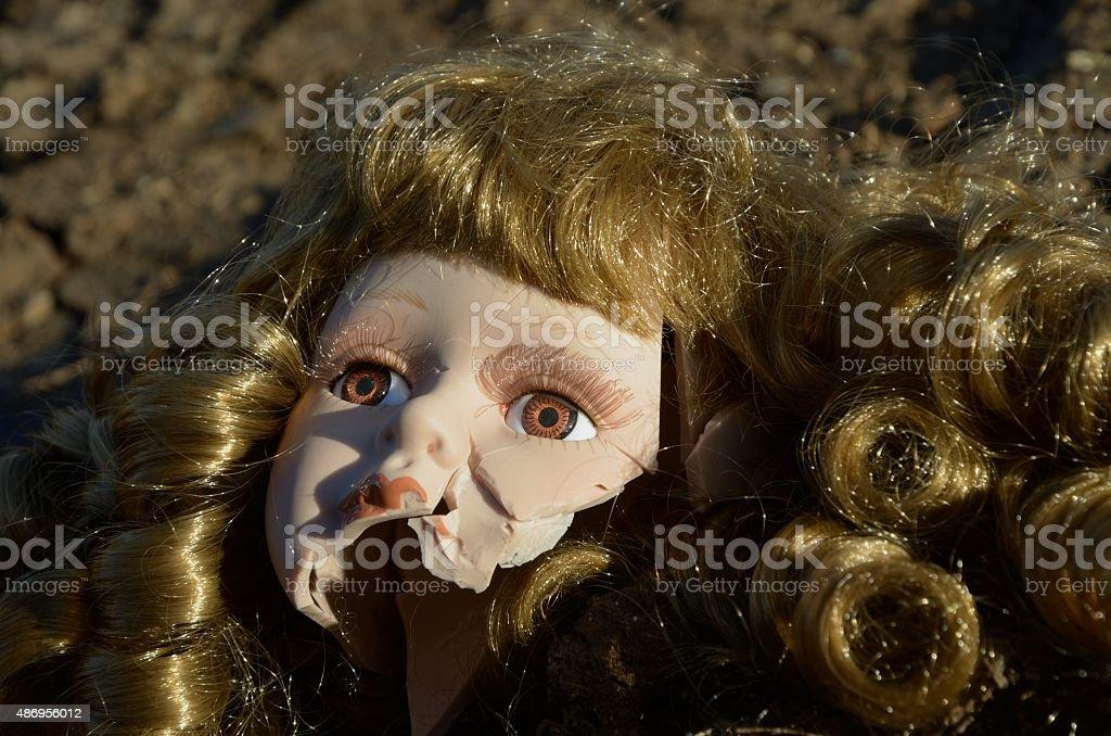 Broken doll head on the ground stock photo