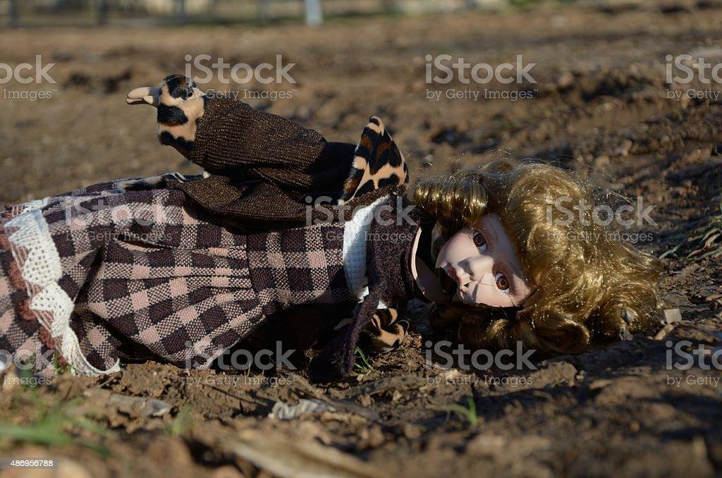 Broken doll on the ground stock photo