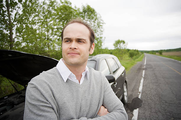 Broken Down Car on Side of Road with Man stock photo