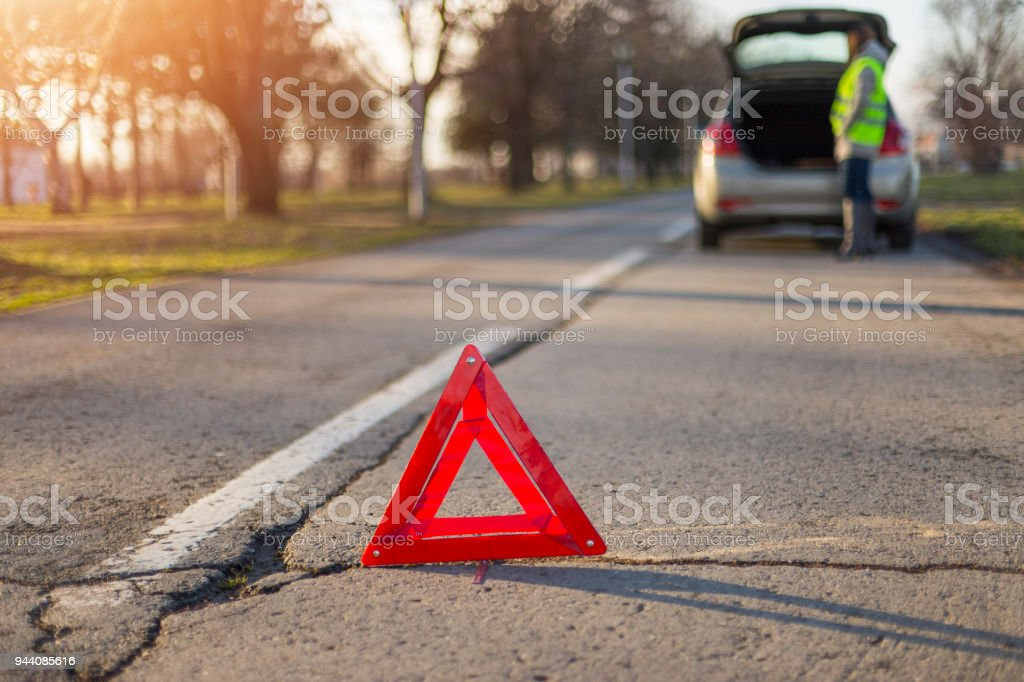 Broken down car with warning triangle. Woman standing alongside her...