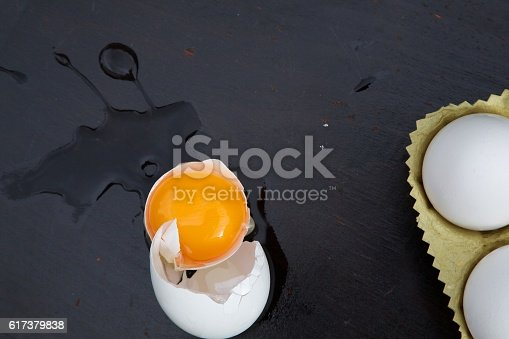 istock Broken egg on a black wooden surface 617379838