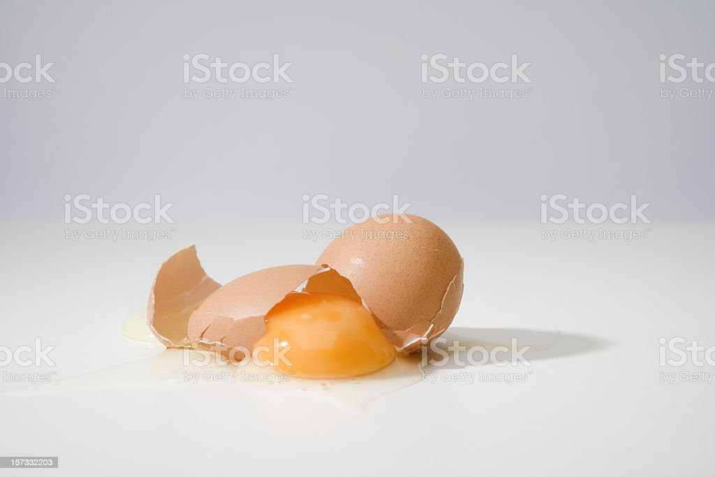 Broken egg on grey background stock photo