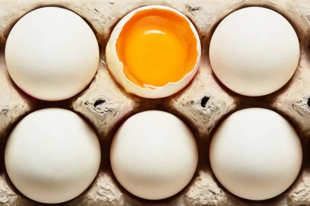 bütün yumurta ile kırık yumurta - yumurta stok fotoğraflar ve resimler