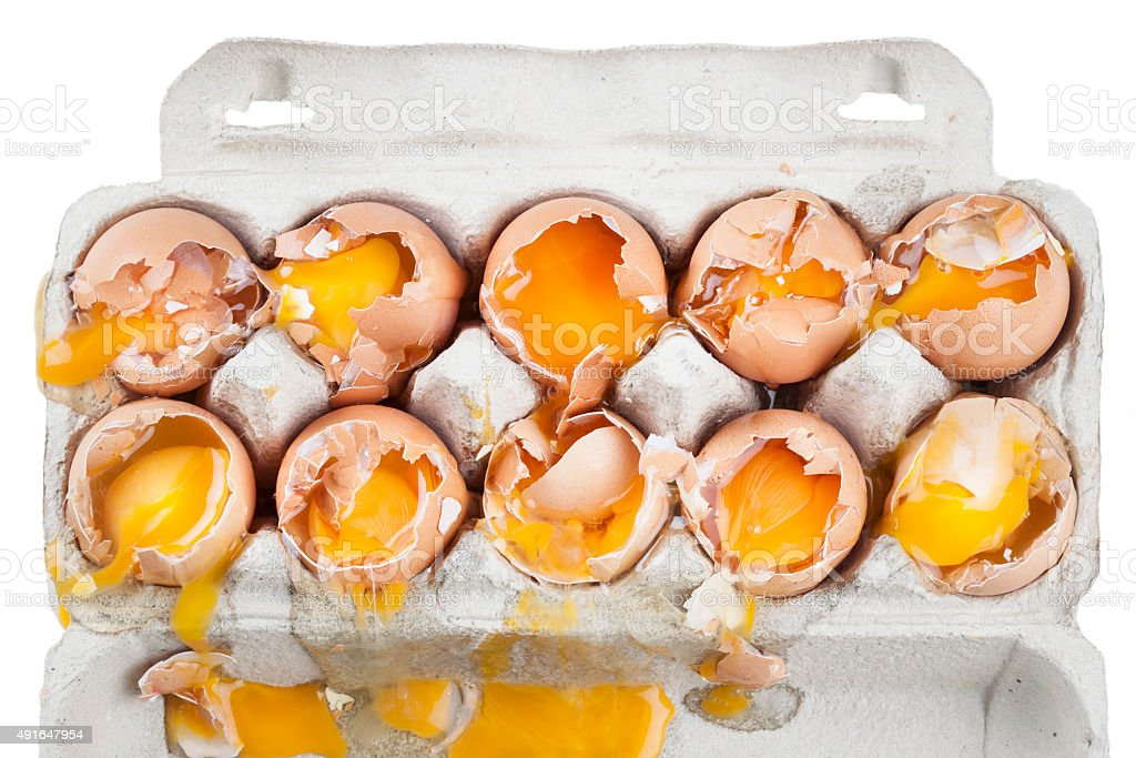 Broken eggs in a box stock photo