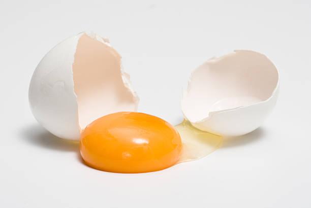 broken eggshells next to egg yolk - yumurta sarısı stok fotoğraflar ve resimler