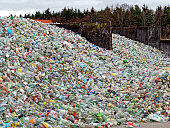 many broken bottles waiting for the next step for recycling at a industrial collection point. detail of a very huge heap.