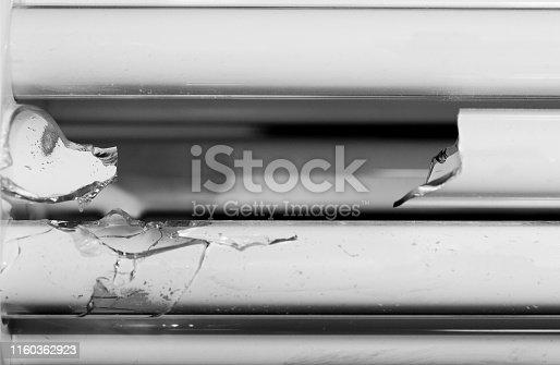 Shattered glass tubes. Broken energy saving bulb, compact fluorescent lamp tubular type.