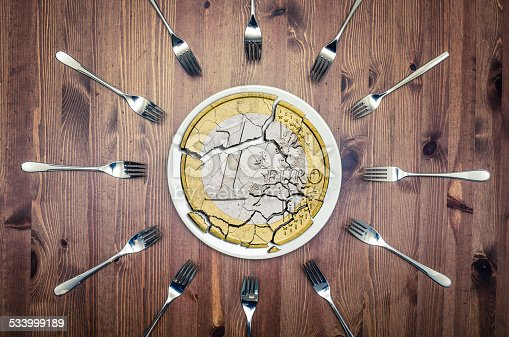 istock broken euro coin on a plate, with many forks around 533999189