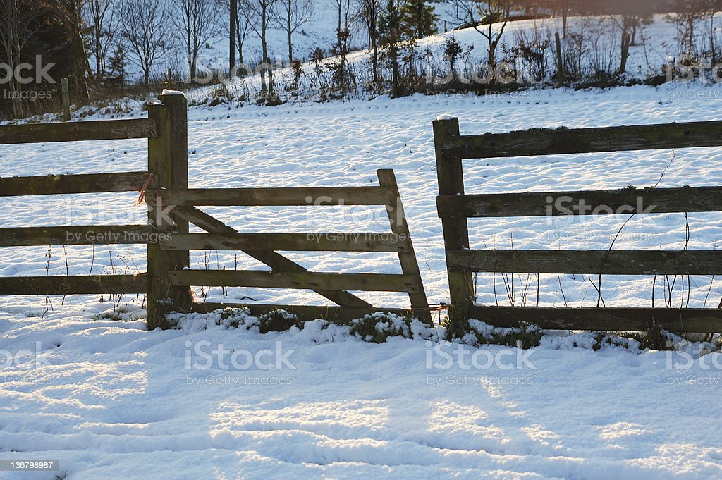 broken fence in the snow at sunset stock photo