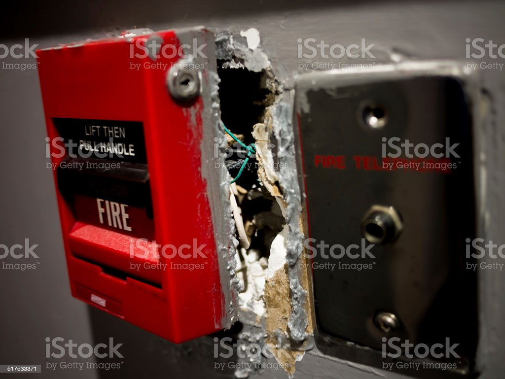 Broken fire alarm on a wall stock photo