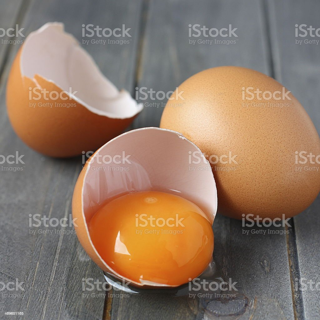 Broken fresh egg on rustic wooden background stock photo