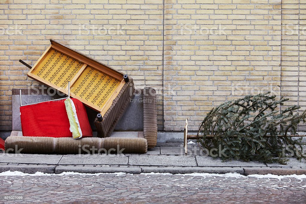 Broken furniture and Christmas tree left on pavement